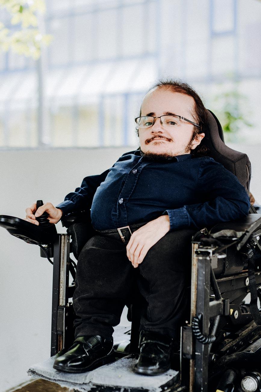 Edwin Greve steht vor einem BVG Bushaltestellen-Schild. Er ist leicht von unten fotografiert und lächelt freudig in die Kamera. Er trägt ein dunkelblaues Hemd, eine schwarze Hose und Lederschuhe. Er hat einen Schnurrbart und einen Kinnbart, trägt eine dunkle Halbrandbrille und hat längere, nach hinten zusammengebundene, dunkle Haare. Seine Arme ruhen auf den Armlehnen des Rollstuhls, am rechten Mittelfinger trägt er einen einfachen silberfarbenen Ring. Im Hintergrund befindet sich eine Art Unterführung, Betonbauten und an der Straße stehen parkende Autos.